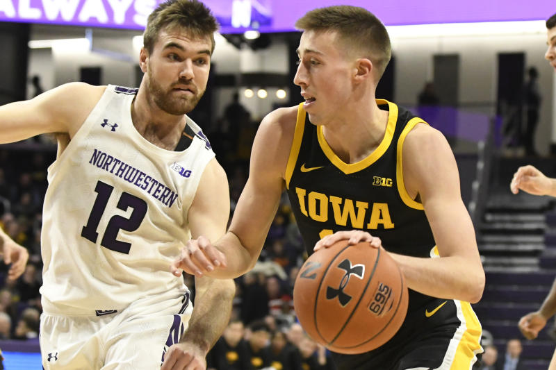 Northwestern guard Pat Spencer (12) defends against Iowa guard Joe Wieskamp (10) during the first half of an NCAA college basketball game Tuesday, Jan. 14, 2020, in Evanston, Ill. (AP Photo/David Banks)
