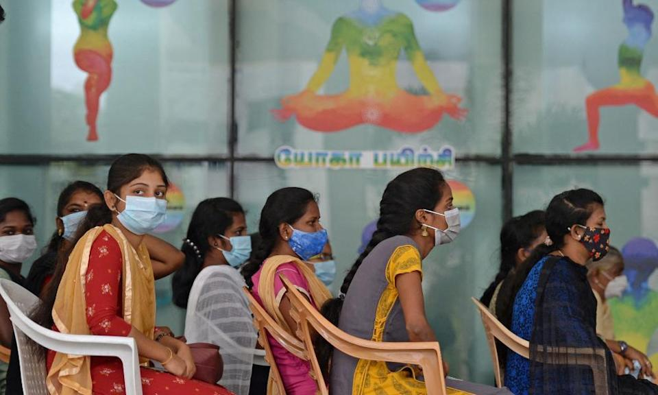 Young frontline workers wait to get vaccinated at a government hospital in Chennai