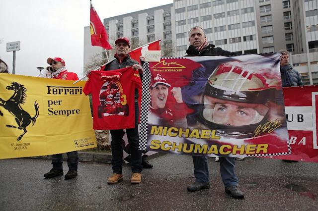 Fans of Michael Schumacher hold banners to honor the Formula One Champion on his 45th birthday, Friday Jan. 3, 2014, in front of the Grenoble hospital where former seven-time Formula One champion Michael Schumacher is being treated after sustaining a head injury during a ski accident. Schumacher has been in a medically induced coma since Sunday, when he struck his head on a rock while on a family vacation. (AP Photo/Thibault Camus)