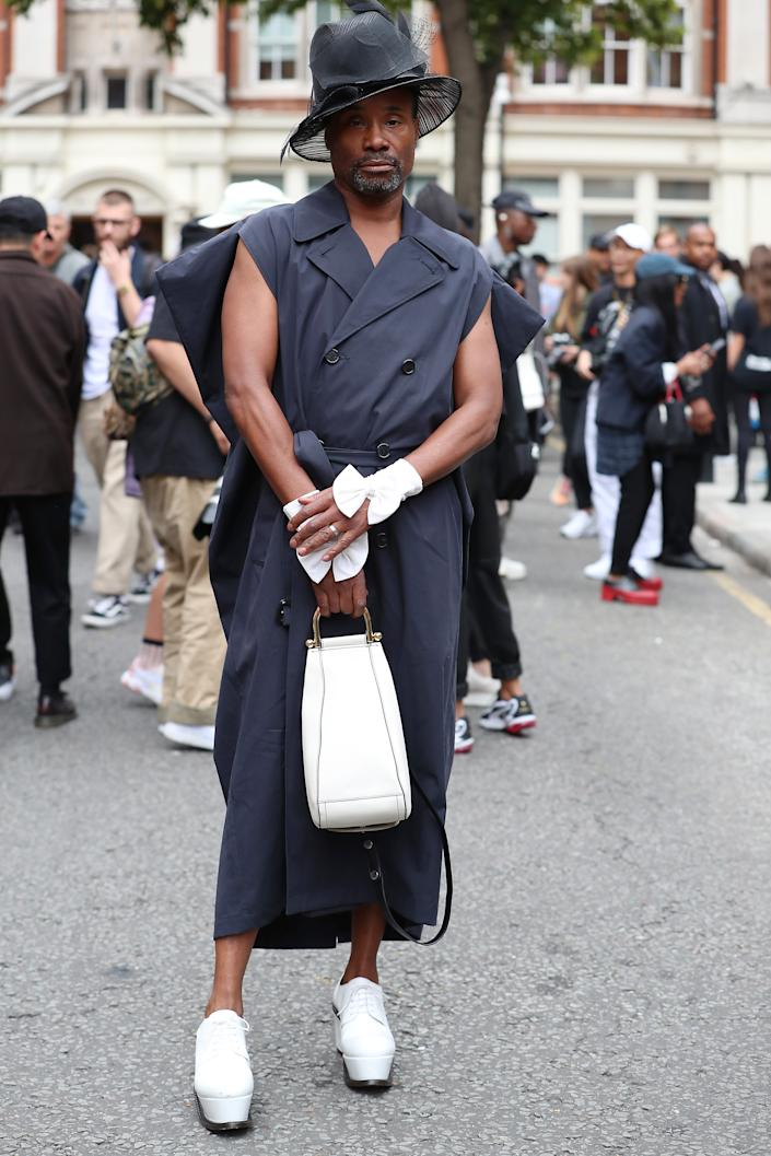 Billy Porter attends the JW Anderson wearing a navy sleeveless trench coat with matching white accessories and black hat [Photo: Getty Images]