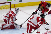Detroit Red Wings goalie Jonathan Bernier, left, makes a save on a shot by Chicago Blackhawks center Carl Soderberg, right, during the third period of an NHL hockey game in Chicago, Saturday, Feb. 27, 2021. (AP Photo/Nam Y. Huh)