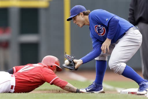 Cincinnati Reds' Shin-Soo Choo, of South Korea, dives safely back to first as Chicago Cubs first baseman Anthony Rizzo catches a pickoff throw in the first inning of a baseball game, Wednesday, April 24, 2013, in Cincinnati. (AP Photo/Al Behrman)