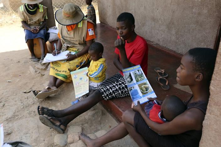 Community health worker, Rosemary Rambire, right, speaks to a young girl during a COVID-19 awareness campaign in Chitungwiza, on the outskirts of Harare, Zimbabwe Wednesday, Sept. 23, 2020. (AP Photo/Tsvangirayi Mukwazhi)