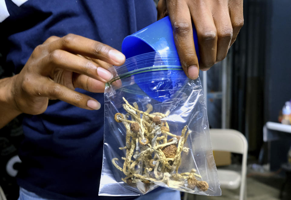 In this Friday, May 24, 2019 photo a vendor bags psilocybin mushrooms at a pop-up cannabis market in Los Angeles. (AP Photo/Richard Vogel)