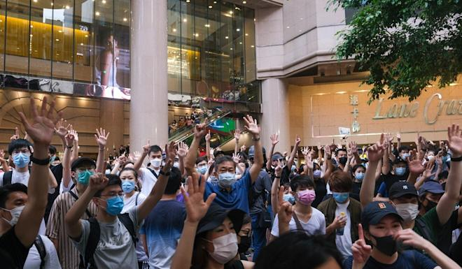 Protesters gesture on July 1, 2020, the day after the sweeping national security law went into effect. Photo: Bloomberg
