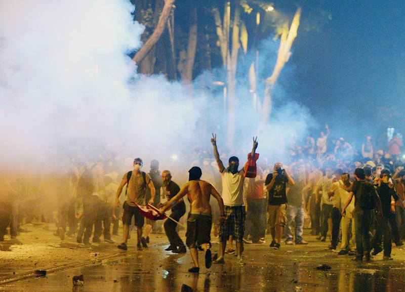 In this photo taken late Saturday, June 1, 2013, Turkish protesters clash with riot police near the former Ottoman palace, Dolmabahce, where Turkey's Prime Minister Recep Tayyip Erdogan maintains an office in Istanbul, Turkey. Protests in Istanbul, Ankara and several other Turkish cities appear to have subsided Sunday, after days of fierce clashes following a police crackdown on a peaceful gathering as protesters denounced what they see as Prime Minister Recep Tayyip Erdogan's increasingly authoritarian style. (AP Photo)