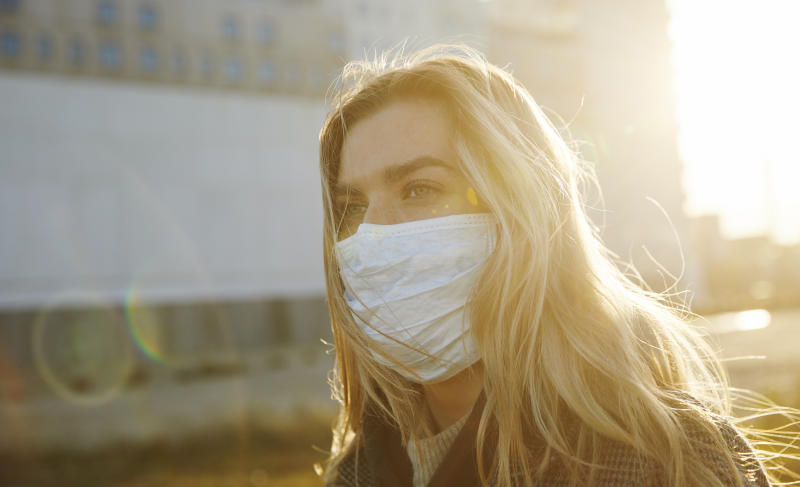 Young woman outside wearing a virus protective face mask