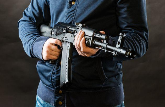 terrorist holding kalashnikov rifle isolated on a black background