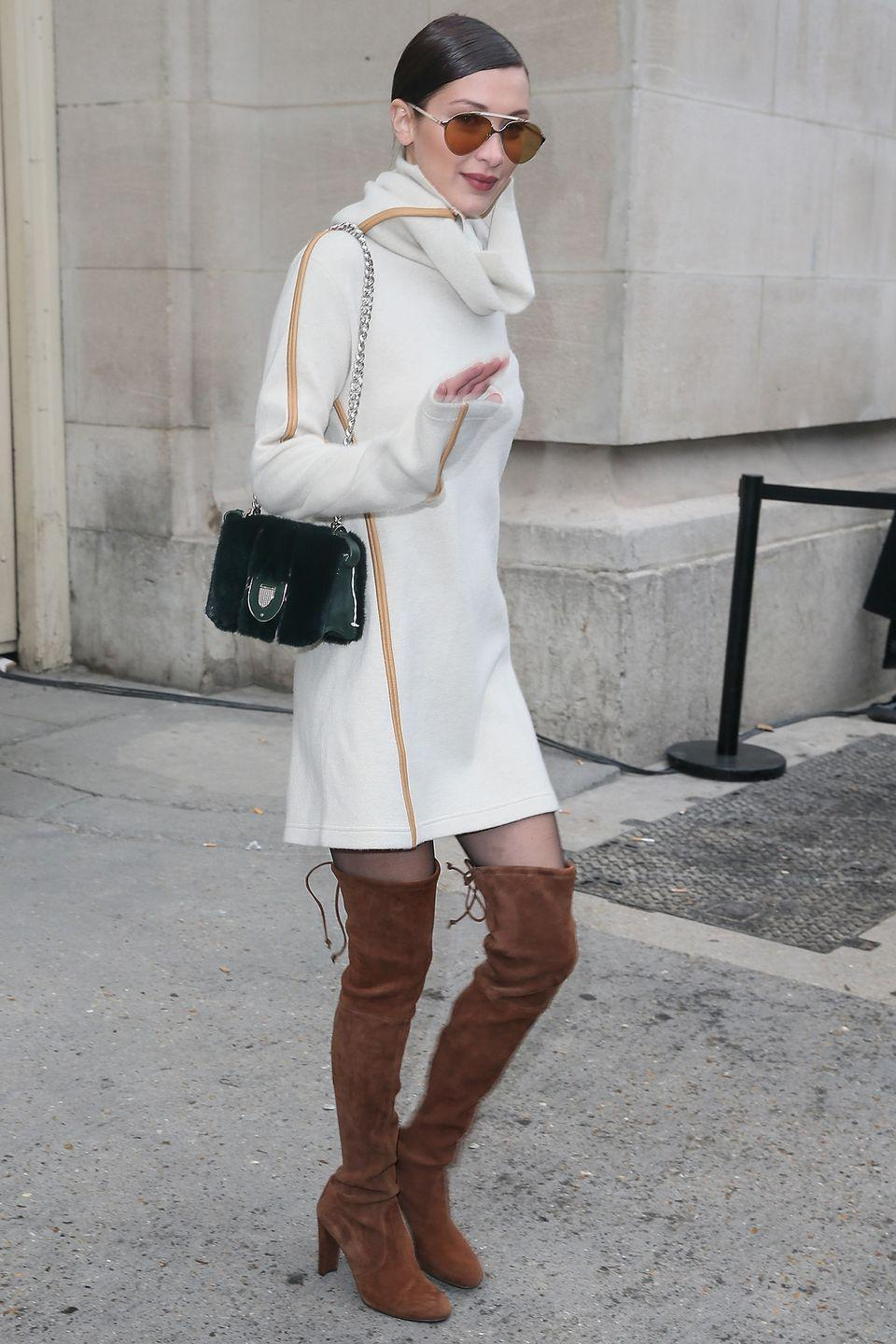 <p>Bella wore a white jumper dress and knee-high brown suede boots as she arrived for the Chanel show during Paris Fashion week, January 2017 </p>