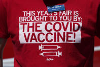 A workers' shirt is seen at a vaccination station at the Iowa State Fair, Monday, Aug. 16, 2021, in Des Moines, Iowa. Visitors are packing in to state fairs in multiple Midwest states as COVID activity is increasing, raising concerns about the potential for rapidly accelerating spread of the delta variant of the COVID-19 virus. (AP Photo/Charlie Neibergall)