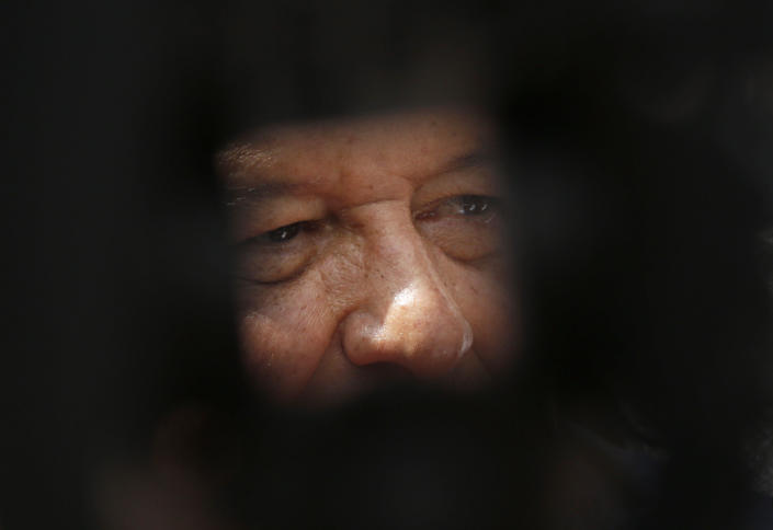 In this photo framed by the leg of a television tripod, Mexico's President Andres Manuel Lopez Obrador talks to the press during a rally to honor the victims of the 1968 Tlatelolco massacre, outside of the Santiago Tlatelolco Church in Mexico City, Tuesday Oct. 2, 2018. Mexico commemorated the 50th anniversary of the massacre of students holding an anti-government protest, killed by men with guns and soldiers ten days before the 1968 Summer Olympics celebrations in Mexico City. (AP Photo/Marco Ugarte)