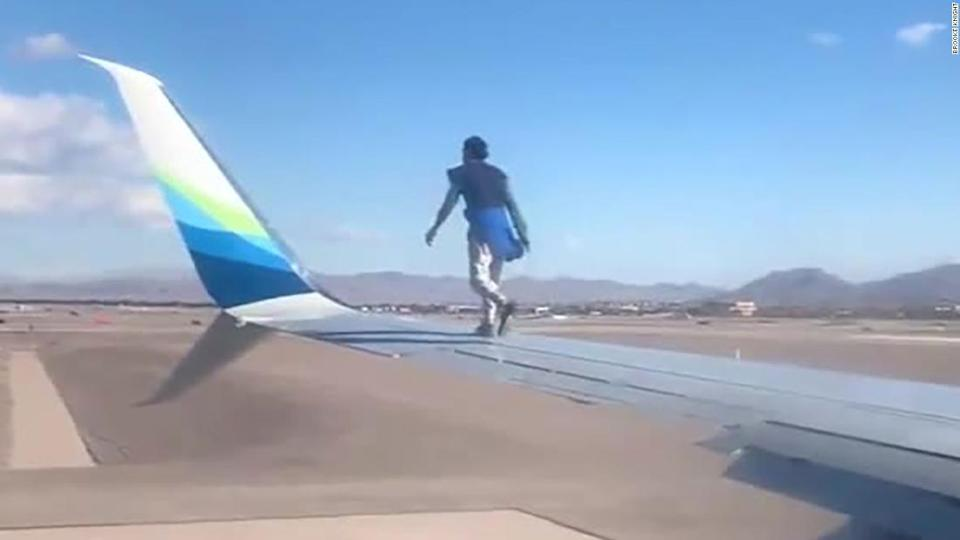 """<p>Authorities took into custody a man who climbed onto the wing of an Alaska Airlines plane minutes before takeoff at McCarran International Airport in Las Vegas on Saturday, December 12.</p><div class=""""cnn--image__credit""""><em><small>Credit: Brooke Knight / Brooke Knight</small></em></div>"""