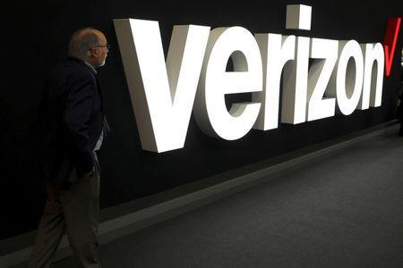 FILE PHOTO: A man stands next to the logo of Verizon at the Mobile World Congress in Barcelona, Spain, February 26, 2019. REUTERS/Sergio Perez/File Photo