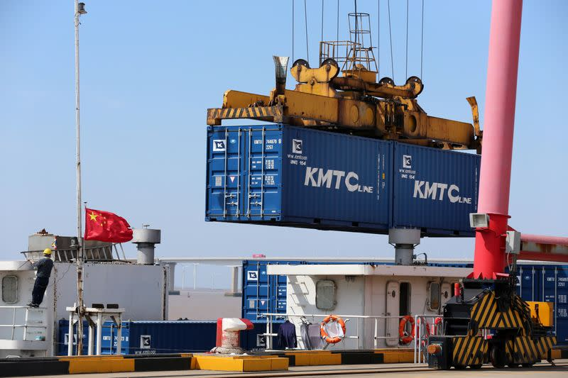 Crane lifts containers to be loaded onto a cargo vessel at a port in Qidong city of Nantong