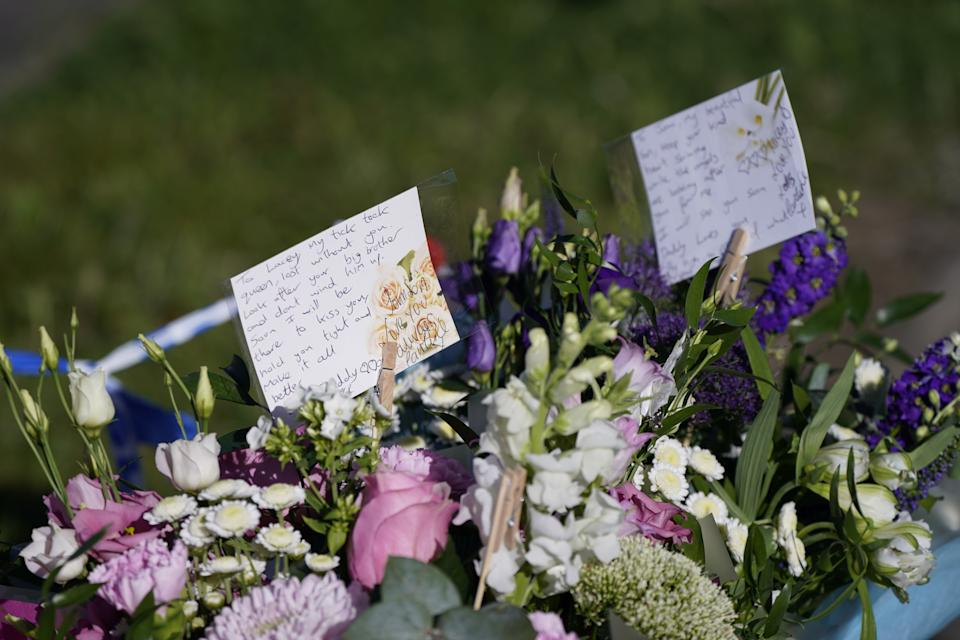 Messages left by the father to two of the victims on bouquets of flowers at the scene in Chandos Crescent, Killamarsh, near Sheffield, where four people were found dead at a house on Sunday. Derbyshire Police said a man is in police custody and they are not looking for anyone else in connection with the deaths. Picture date: Monday September 20, 2021.