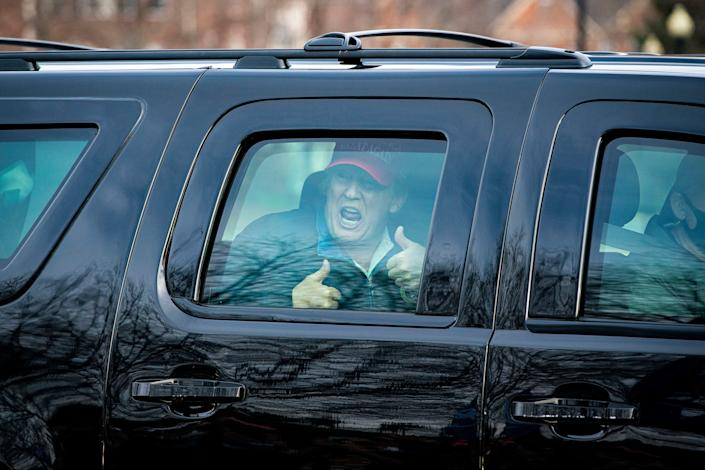 President Donald Trump gives a thumbs up towards supporters as he departs Trump National Golf Club on Dec. 13, 2020, in Sterling, Virginia.