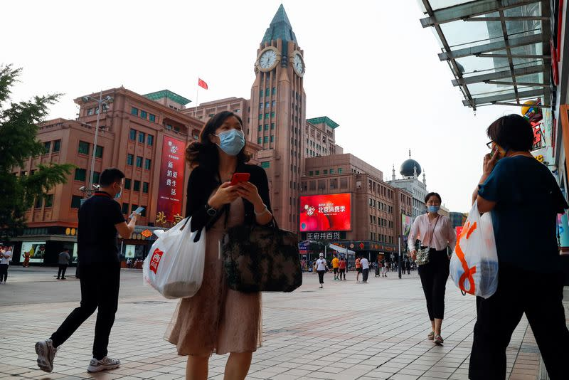 FILE PHOTO: People walk past a department store of the Wangfuijing Group in Beijing