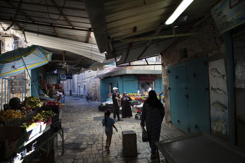 In this Tuesday, Sept. 24, 2019 photo, Israeli Arabs walk at the market in the old city of Acre, northern Israel. Electoral gains made by Arab parties in Israel, and their decision to endorse one of the two deadlocked candidates for prime minister, could give them new influence in parliament. But they also face a dilemma dating back to Israel's founding: How to participate in a system that they say relegates them to second-class citizens and oppresses their Palestinian brethren in Gaza and the occupied West Bank. (AP Photo/Oded Balilty)