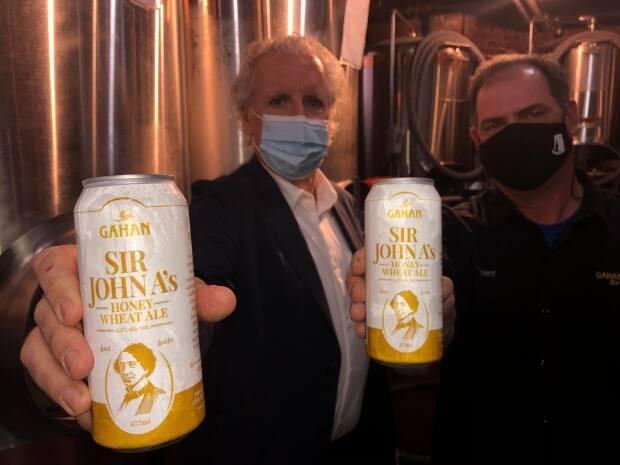 Kevin Murphy and brewmaster Trent Hayes with cans of Sir John A.'s Honey Wheat Ale. (Brian Higgins/CBC - image credit)