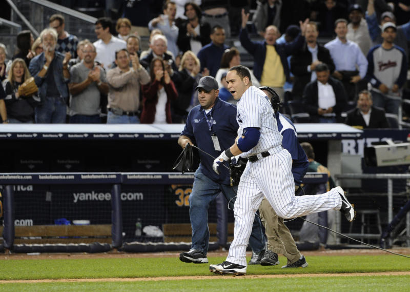 Fans cheer as New York Yankees' Russell Martin runs down the third base line headed to home plate after hitting a solo home run off Oakland Athletics relief pitcher Sean Doolittle to give the Yankees a 2-1 win, in the 10th inning of a baseball game Friday, Sept. 21, 2012, at Yankee Stadium in New York. (AP Photo/Kathy Kmonicek)