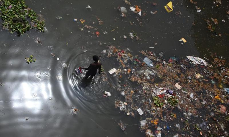 A scavenger looks for recyclable items on the banks of the Yamuna river.
