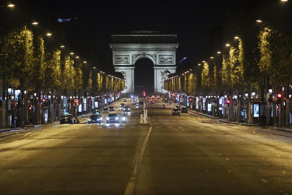 Champs-Elysees avenue is almost empty during curfew in Paris, Saturday, Oct. 17, 2020. French restaurants, cinemas and theaters are trying to figure out how to survive a new curfew aimed at stemming the flow of record new coronavirus infections. The monthlong curfew came into effect Friday at midnight, and France is deploying 12,000 extra police to enforce it. (AP Photo/Lewis Joly)
