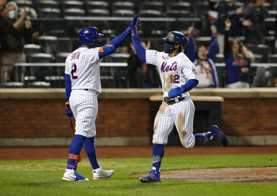 New York Mets' Francisco Lindor (12) is congratulated by Dominic Smith (2) after scoring against the Arizona Diamondbacks during the third inning of a baseball game Saturday, May 8, 2021, in New York. (AP Photo/Noah K. Murray)