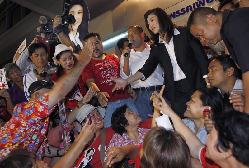 Yingluck Shinawatra, opposition Pheu Thai Party's candidate for prime minister shakes hands with supporters as she celebrates after winning the election at the party headquarters in Bangkok on Sunday, July 3, 2011.  The sister of exiled former Prime Minister Thaksin Shinawatra, Yingluck led Thailand's main opposition party to a landslide victory in elections Sunday, heralding an extraordinary political turnaround five tumultuous years after her fugitive billionaire brother was toppled in an army coup, and paving the way Yingluck Shinawatra, who has never held office, to become this Southeast Asian kingdom's first female prime minister. (AP Photo/Vincent Yu)