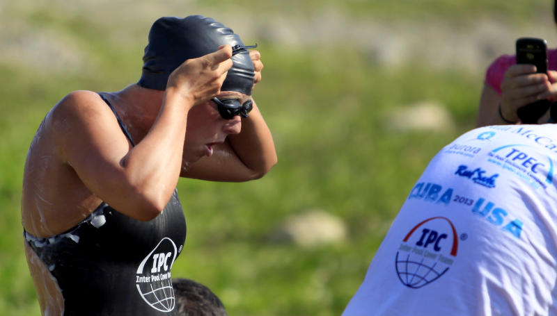 Australian swimmer Chloe McCardel puts on her goggles as she prepares to jump into the water and start her swim to Florida from Havana, Cuba, Wednesday, June 12, 2013. The Australian endurance athlete is hoping to become the first person to swim from Havana to Florida without a protective shark cage. McCardel says she expects to spend about 60 hours in the sea before reaching the Florida Keys, a little more than 100 miles to the northeast. (AP Photo/Ramon Espinosa)