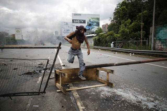 <p>A demonstrator jumps over a barricade during a national sit-in against President Nicolas Maduro, in Caracas, Venezuela, Monday, May 15, 2017. (AP Photo/Ariana Cubillos) </p>