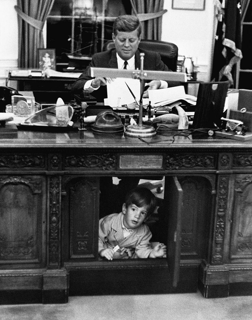 <p>John Jr. plays under his father's desk in the Oval Office, while the President works in the background. </p>
