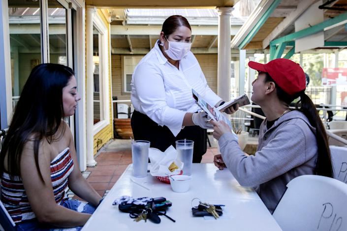 Dayana Solia takes menus from customers Lexie Belche, left, and Aleza Ruiz at Juan in a Million on East Cesar Chavez Street in Austin, Texas, on May 1. Ruiz called the restaurant at 7 a.m. to see if it was open after Gov. Greg Abbott ordered the gradual reopening of Texas businesses amid the coronavirus outbreak. All retail stores, malls, restaurants, movie theaters, libraries and museums must limit customers to 25% of their listed occupancy.