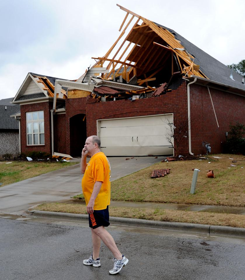 Stanley Nelson talks on his cell phone in front of his damaged home  in Athens, Ala. on Friday, March 2, 2012. A reported tornado destroyed several houses in northern Alabama as storms threatened more twisters across the region Friday (AP Photo/The Decatur Daily, Gary Cosby Jr.)