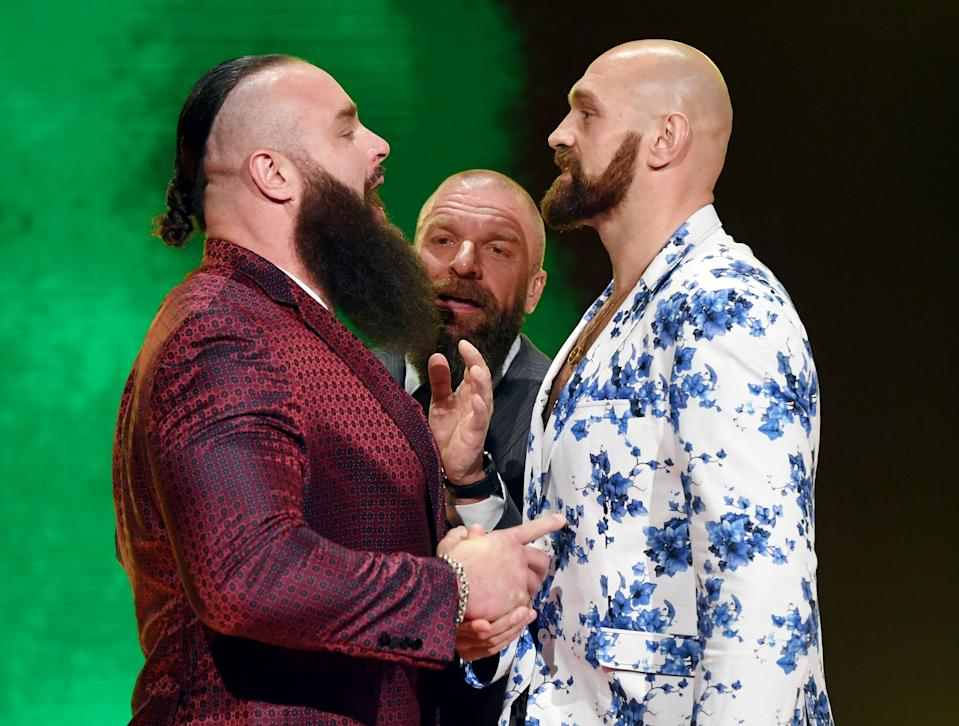 """LAS VEGAS, NEVADA - OCTOBER 11:  WWE Executive Vice President of Talent, Live Events and Creative Paul """"Triple H"""" Levesque (C) gets between WWE wrestler Braun Strowman (L) and heavyweight boxer Tyson Fury (R) as they face off during the announcement of their match at a WWE news conference at T-Mobile Arena on October 11, 2019 in Las Vegas, Nevada. Strowman will face Fury and WWE champion Brock Lesnar will take on former UFC heavyweight champion Cain Velasquez at the WWE's Crown Jewel event at Fahd International Stadium in Riyadh, Saudi Arabia on October 31.  (Photo by Ethan Miller/Getty Images)"""
