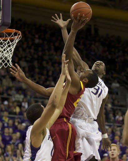 Byron Wesley, center, of USC goes to the hoops as he is defend by Washington's Abdul Gaddy, left, and Terrence Rossduring play in an NCAA college basketball game at Alaska Airlines Arena in Seattle Saturday Feb. 4, 2012. (AP Photo/Stephen Brashear)