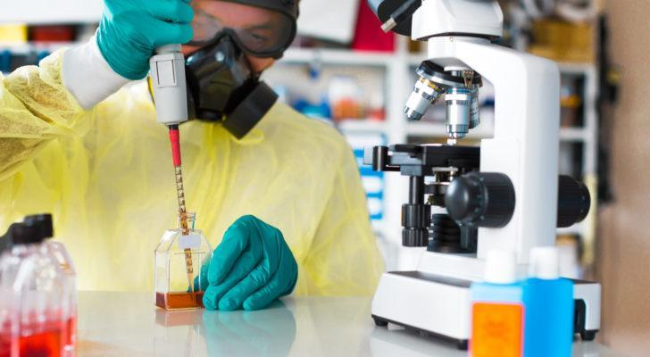 a scientist with protective equipment and microscope in a lab JAGX stock