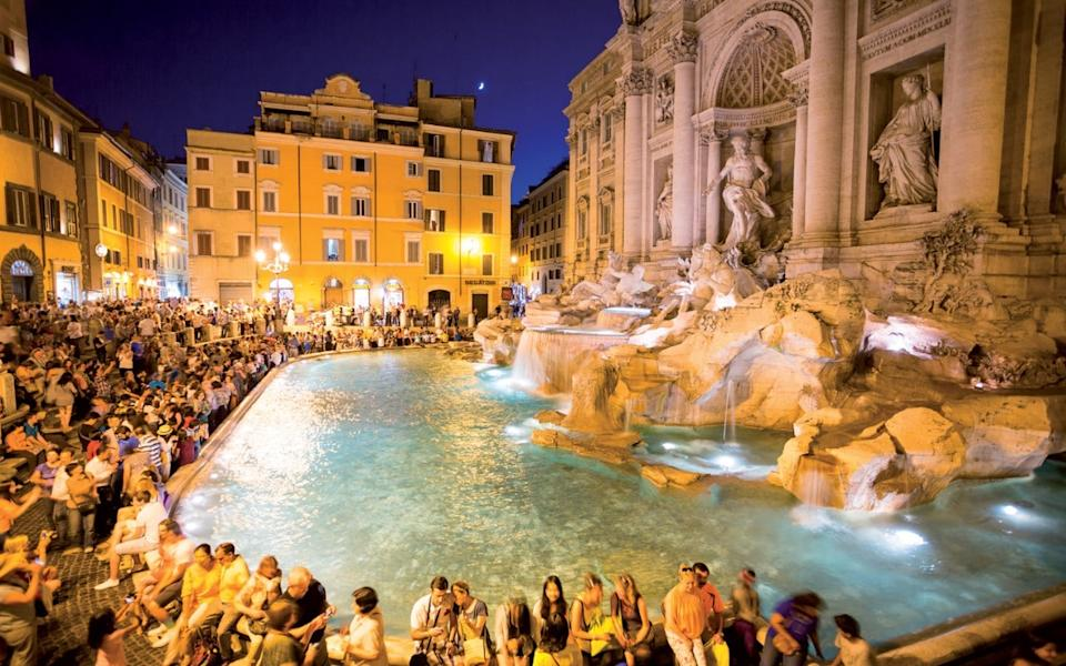 A crowd of people gather around Rome's Trevi Fountain during the evening