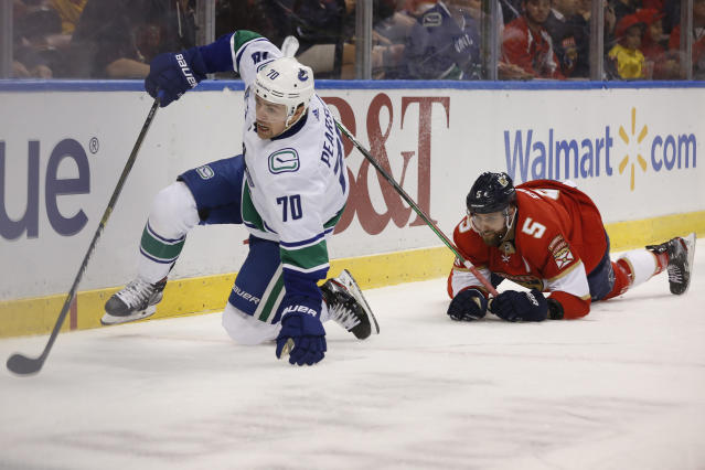 Vancouver Canucks left wing Tanner Pearson (70) and Florida Panthers defenseman Aaron Ekblad (5) trip while going for the puck during an NHL hockey game Thursday, Jan. 9, 2020, in Sunrise, Fla. (AP Photo/Brynn Anderson)