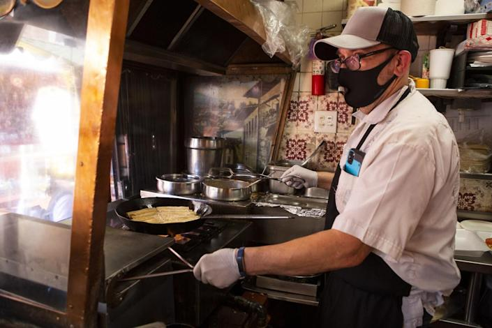 Edward Flores, wearing a mask, holds tongs while cooking at a stovetop in his restaurant