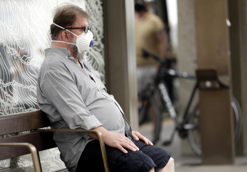 FILE - In this Jan. 2, 2020, file photo, a commuter wears a mask as smoke shrouds the Australian capital of Canberra, Australia. It's an unprecedented dilemma for Australians accustomed to blue skies and sunny days that has raised fears for the long-term health consequences if prolonged exposure to choking smoke becomes the new summer norm. (AP Photo/Mark Baker, File)