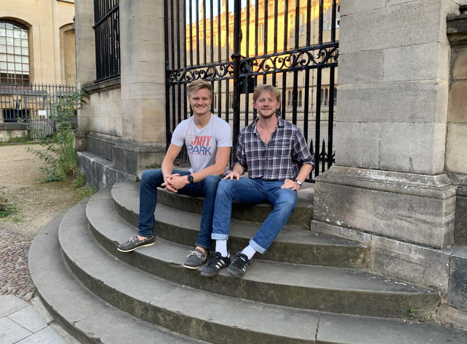 Heimdal founders Marcus Lima (left) and Erik Millar sitting by a metal gate on stone steps..