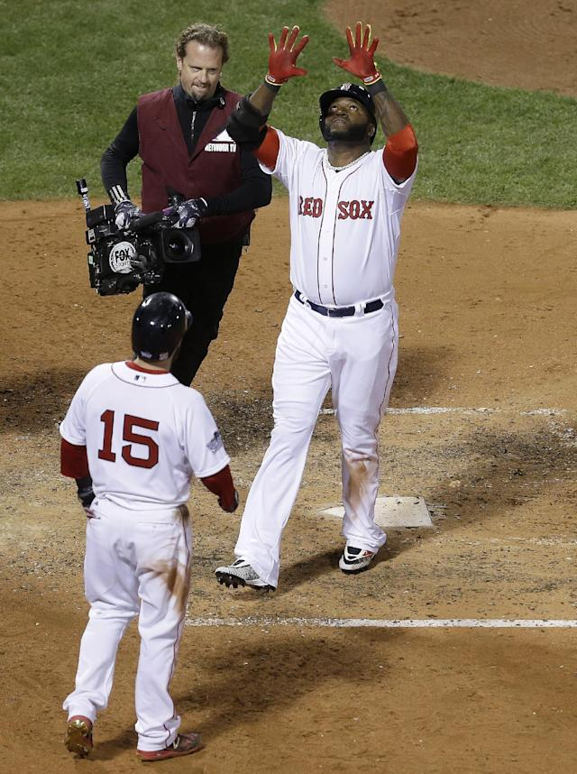 Boston Red Sox's David Ortiz celebrates as he crosses home after hitting a two-run home run during the seventh inning of Game 1 of baseball's World Series against the St. Louis Cardinals Wednesday, Oct. 23, 2013, in Boston. Dustin Pedroia (15) scored on the homer. (AP Photo/David J. Phillip)