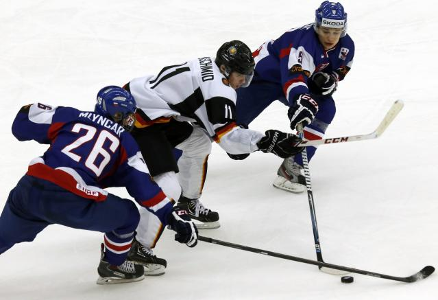 Germany's Markus Eisenschmid (C) fights for the puck with Slovakia's Filip Mlyncar (L) and Michal Valjent during the second period of their IIHF World Junior Championship ice hockey game in Malmo December 27, 2013. REUTERS/Alexander Demianchuk (SWEDEN - Tags: SPORT ICE HOCKEY)