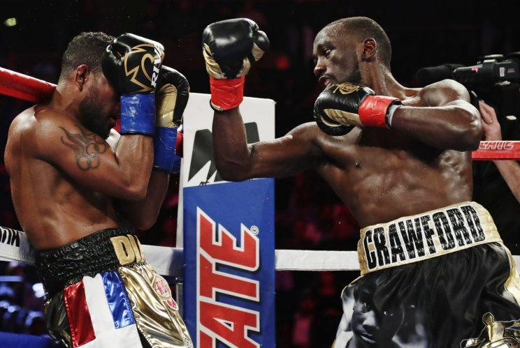 Felix Diaz (L) tries unsuccessfully to fend off Terence Crawford during their super lightweight title fight Saturday in New York. (The Associated Press)