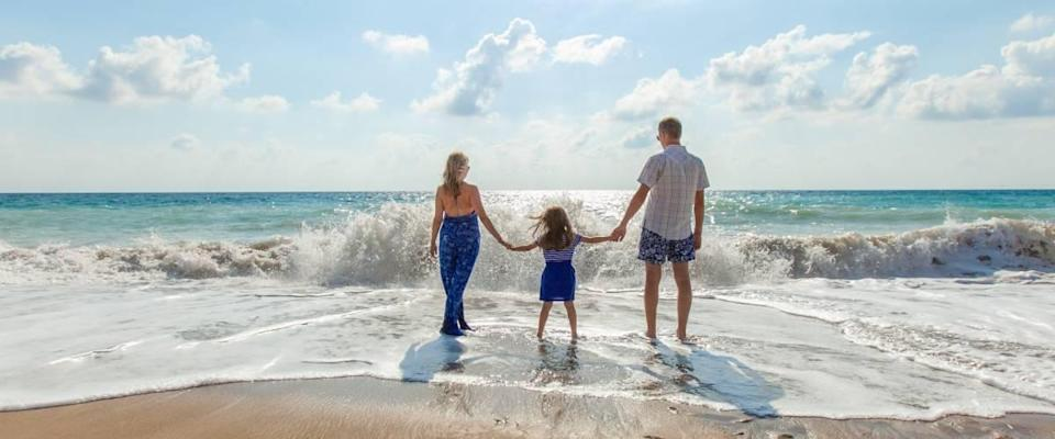 Parents and small child holding hands on beach
