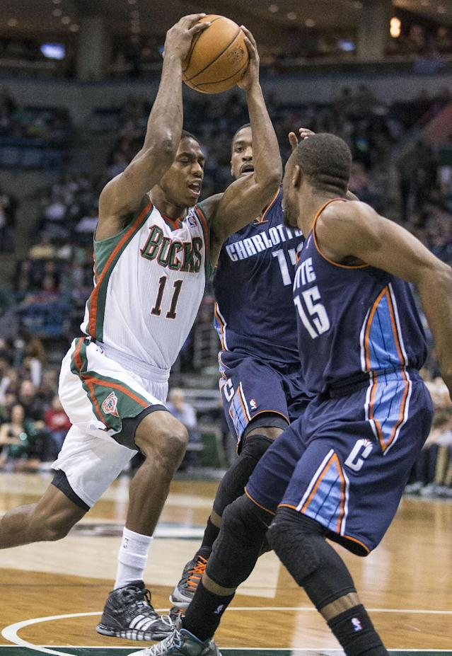 Milwaukee Bucks' Brandon Knight (11) drives between Charlotte Bobcat defenders Michael Kidd-Gilchrist and Kemba Walker (15) during the second half of an NBA basketball game on Sunday, March 16, 2014, in Milwaukee. (AP Photo/Tom Lynn)