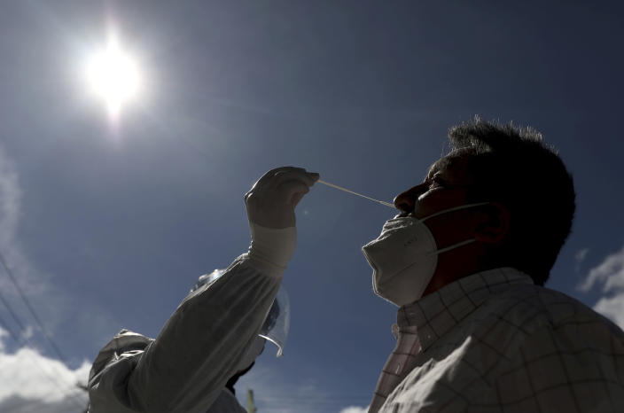 A healthcare worker collects a nasal swab sample to test for COVID-19, in Bogota, Colombia, Wednesday, Jan. 27, 2021. The Colombian government announced that the first shipment of new coronavirus vaccines will arrive in February. (AP Photo/Fernando Vergara)