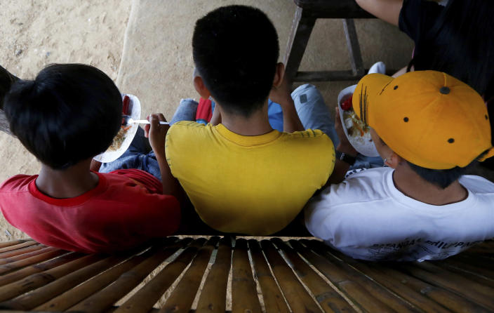 In this Jan. 27, 2019 photo, three boys have a snack at a beach resort in Talustusan on Biliran Island in the central Philippines. Since December 2018, the small village has been rocked by controversy after about 20 boys and men, including these three, accused their Catholic parish priest Father Pius Hendricks of years of alleged sexual abuse. (AP Photo/Bullit Marquez)