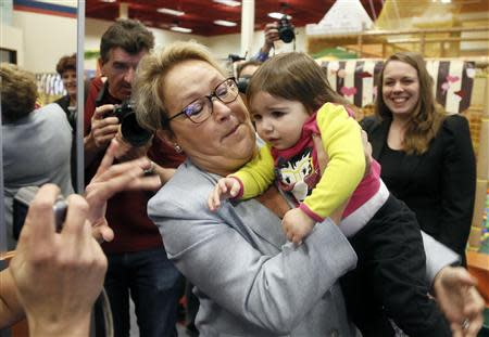 Parti Quebecois leader Pauline Marois holds a child at a children's indoor play centre in Blainville