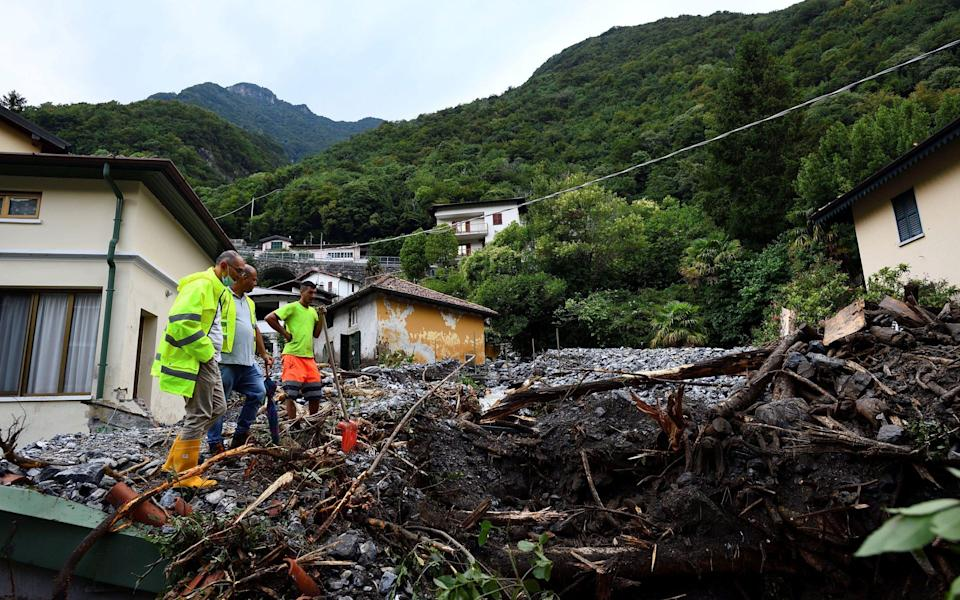 People stand in an area where a landslide has destroyed several houses after heavy rain caused flooding in towns surrounding Lake Como - FLAVIO LO SCALZO /REUTERS